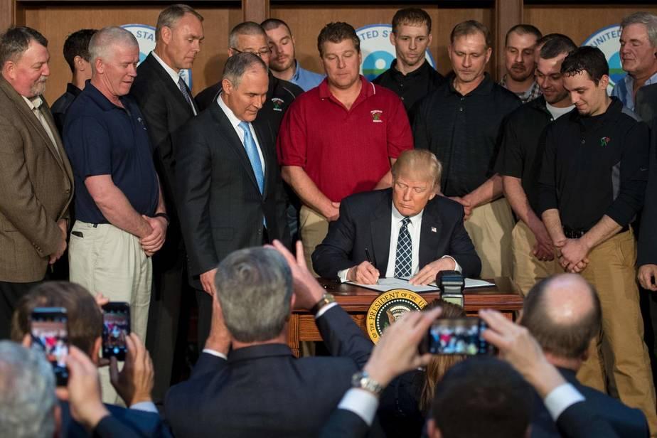 Circondato dai minatori della Rosebud Mining Company, il presidente Trump firma l'ordine esecutivo per l'indpendenza energetica presso la sede dell'EPA a Washington, DC il 28 Marzo 2017.