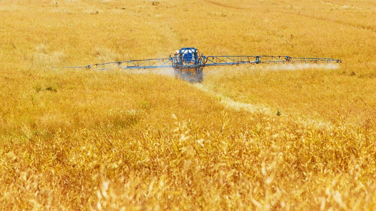 Un trattore sparge pesticidi in un               campo coltivato. Credit: Pixabay.