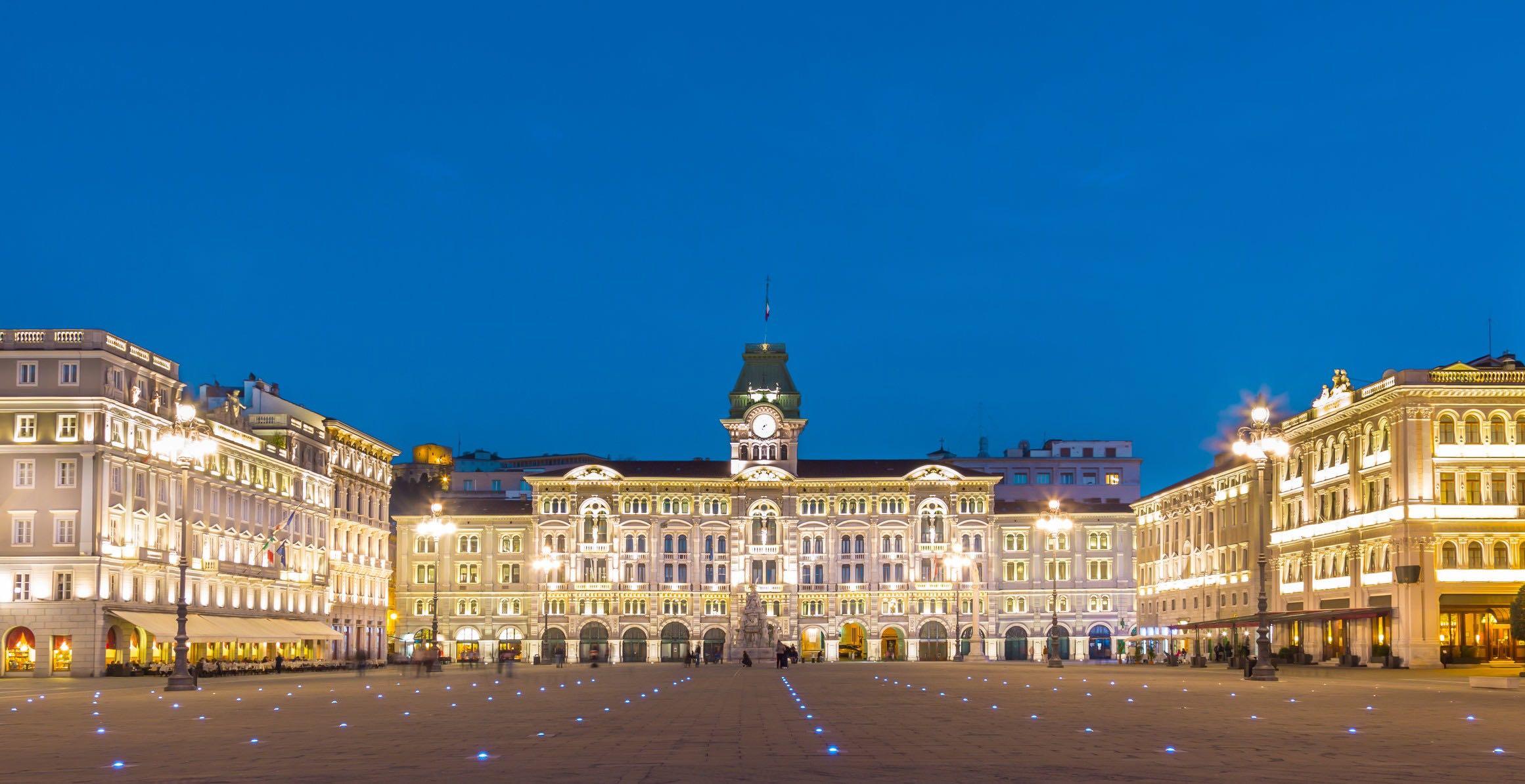 Il palazzo del municipio in Piazza Unità d'Italia a Trieste illuminata al crepuscolo. Credit: Kasto/depositphotos.