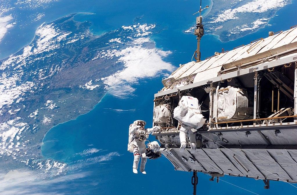 Nell'immagine: l'astronauta della NASA Robert L. Curbeam, Jr., a sinistra, e l'astronauta dell'ESA Christer Fuglesang, impegnati nella prima delle tre sessioni di attività extraveicolari della missione STS-116 mission. Sullo sfondo sono visibili le due isole principali della Nuova Zelanda: l'Isola del Sud, a sinistra, e l'Isola del Nord, a destra. Credit: NASA / Wikipedia. Licenza: Public Domain.