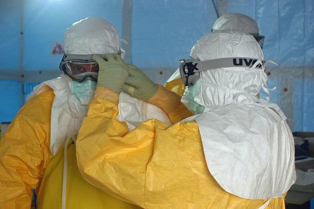 Un operatore sanitario aiuta Jordan Tappero, allora direttore della divisione Global Health Protection dei CDC a indossare la maschera protettiva prima di entrare nell'unità di trattamento di Ebola ELWA 3 allestita da Medici Senza Frontiere ad agosto del 2014 a Monrovia in Liberia. Credit: CDC Global / Flickr. Licenza: CC BY 2.0.