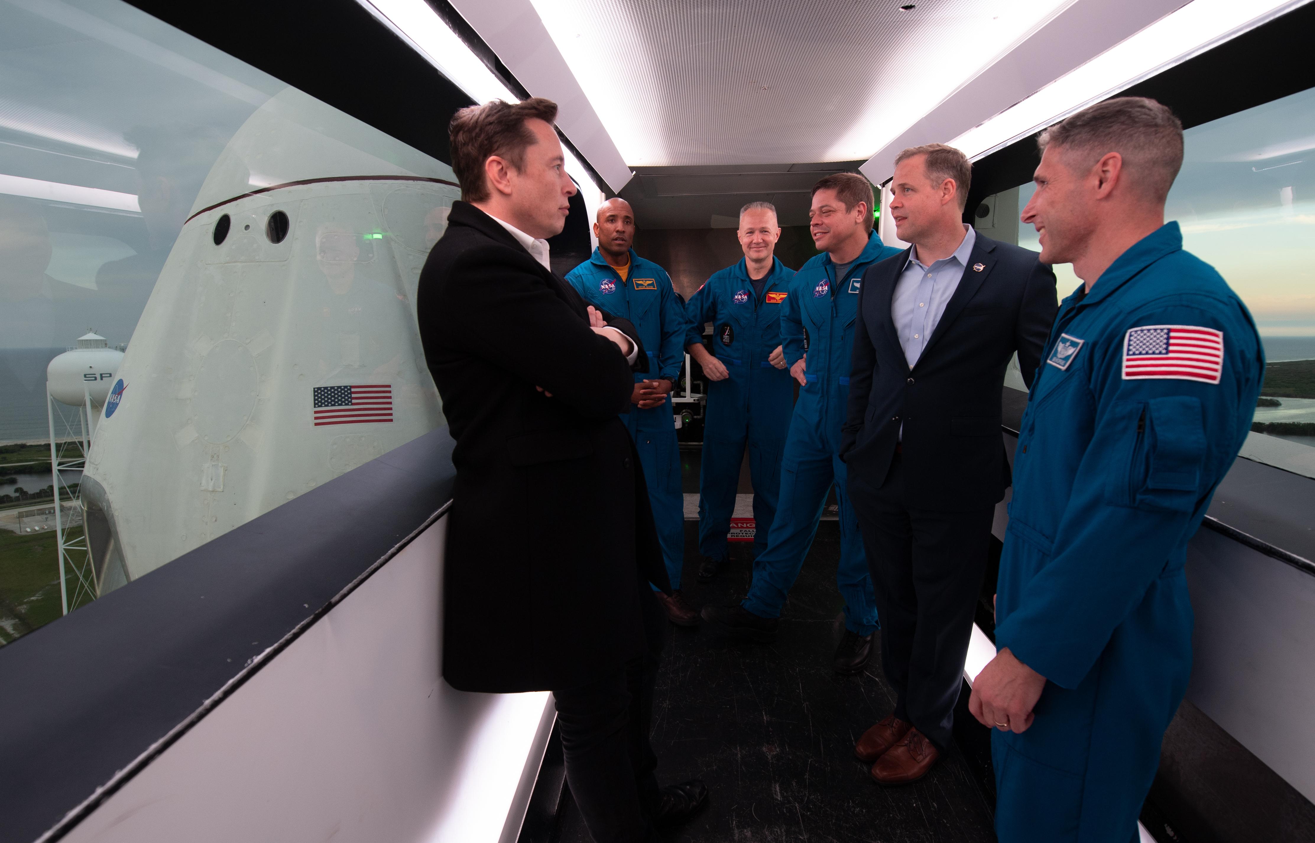 Elon Musk, CEO di SpaceX insieme               agli austronauti della NASA Victor Glover, Doug Hurley,               Bob Behnken, Mike Hopkins e all'amministratore della               NASA Jim Bridenstine all'interno del braccio di accesso               dell'equipaggio nella stazione di lancio di Cape               Canaveral in Florida. Sullo sfondo la navicella spaziale               Crew Dragon. La foto è stata scattata il 1° marzo 2019, il giorno precedente al               lancio della missione Demo-1 del Commercial Crew               Program della NASA.